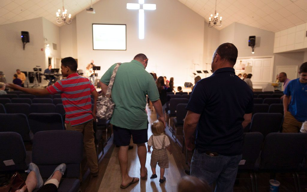 A father and son walk up the aisle to receive communion during the Sunday service at Luke 10:27.