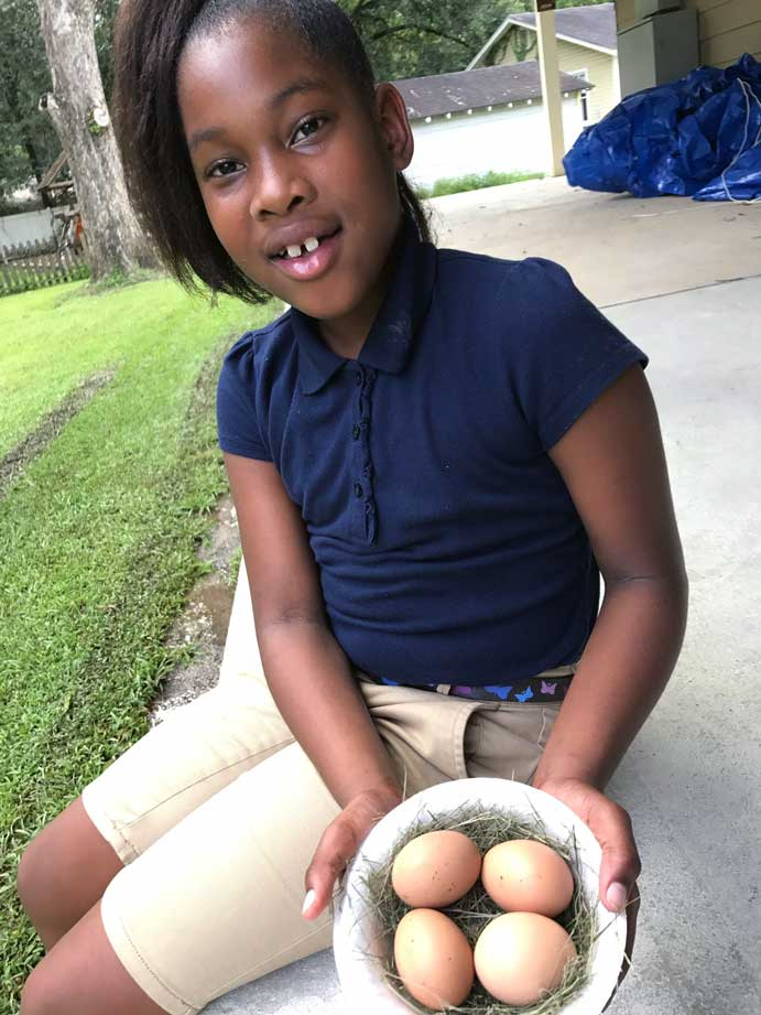 A child participating in The LANDers after school program at the Luke Church in Denham Springs shows off her eggs.