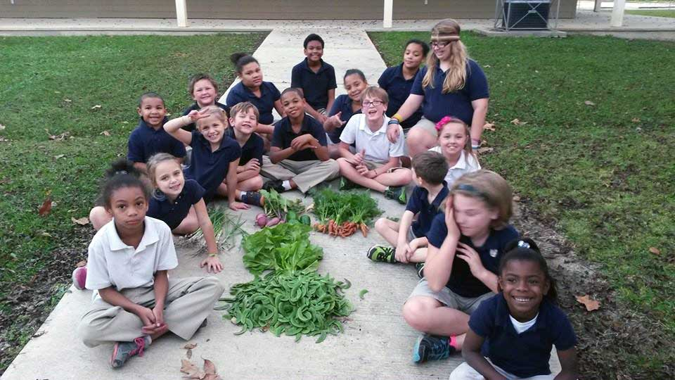 The LANDers kids show off the vegetables they grew in the garden behind The Mission House at Luke 10:27 in Denham Springs.