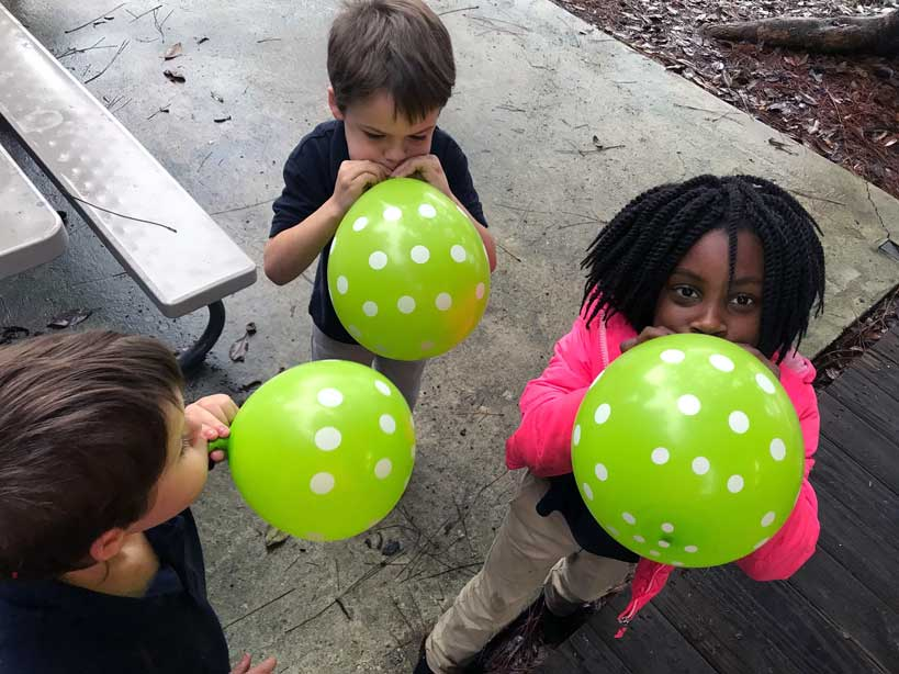 LANDers kids blow balloons while participating in the after school program at the Luke Church in Denham Springs.